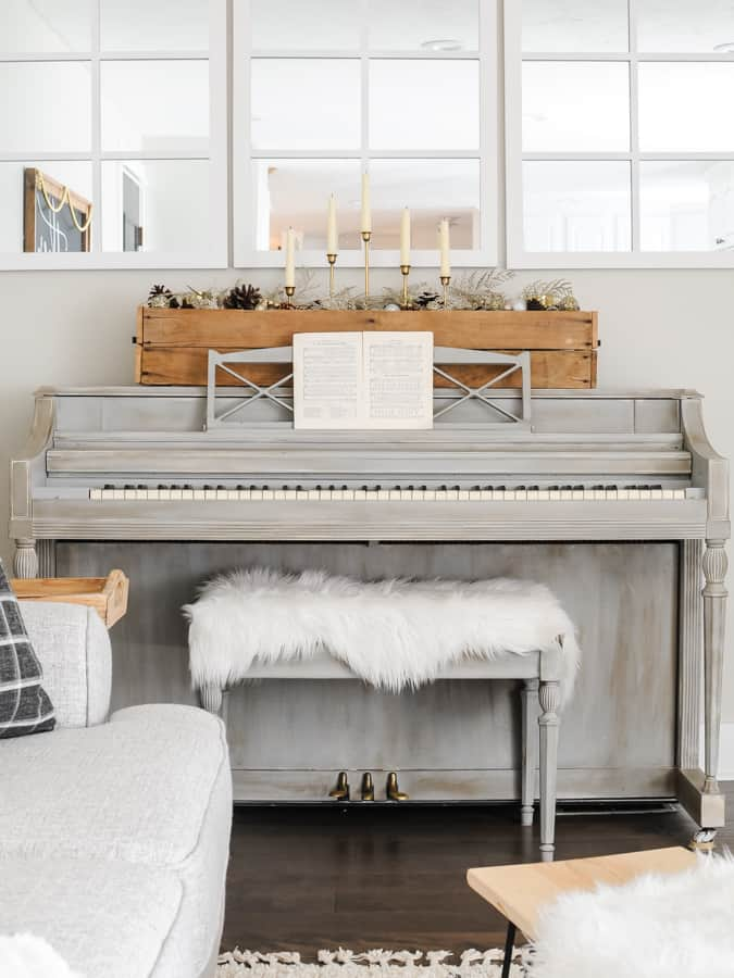 Grey piano with a pallette box of winter decorations (not christmas) and fur rug on the bench.