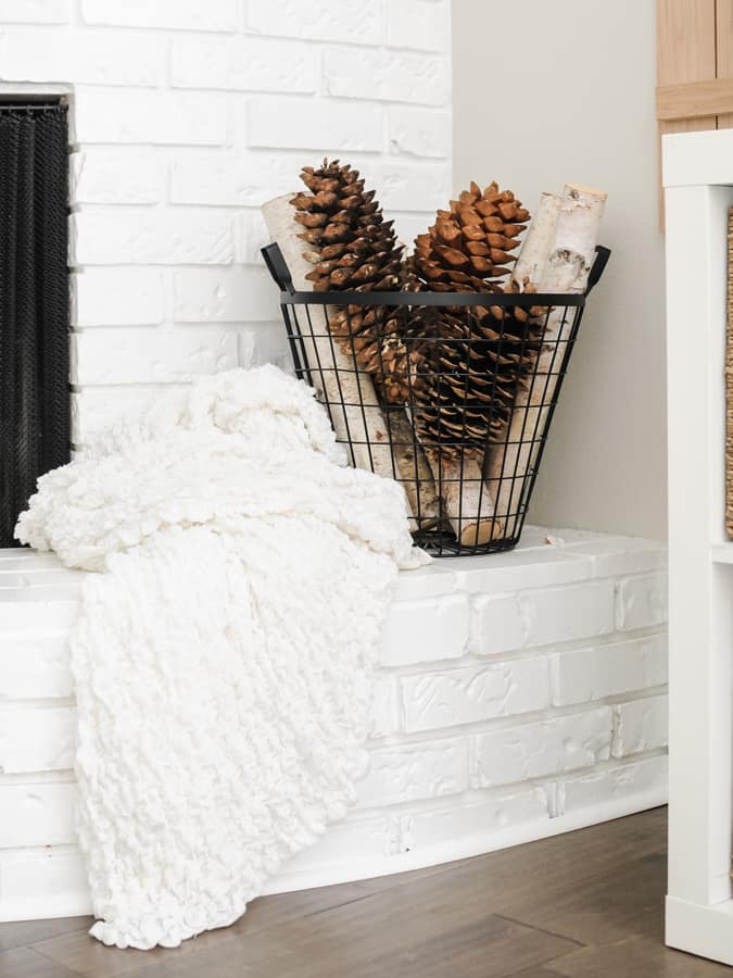 Black basket of large pine cones and birch logs on a white brick hearth.