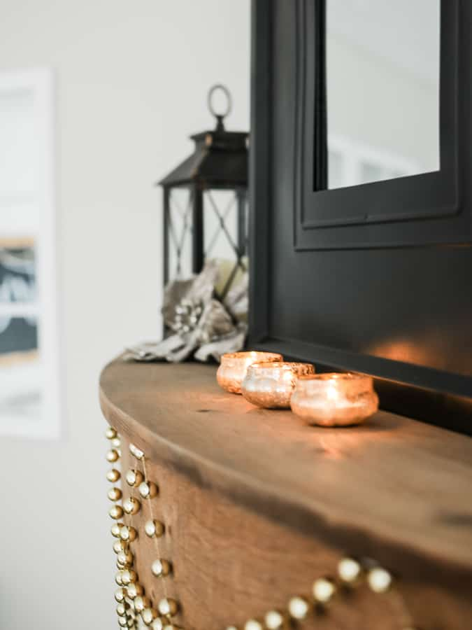 Small mercury glass candle holders on a wood mantel for winter.