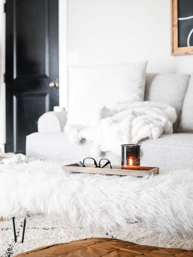 Candle and glasses on a tray atop a faux fur blanket on a winter coffee table.