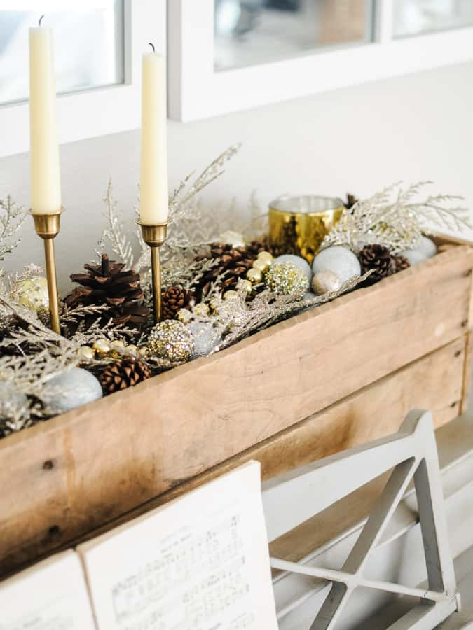 Palette box filled with winter leaves, pinecones, candles and balls for a non-christmas winter decor.