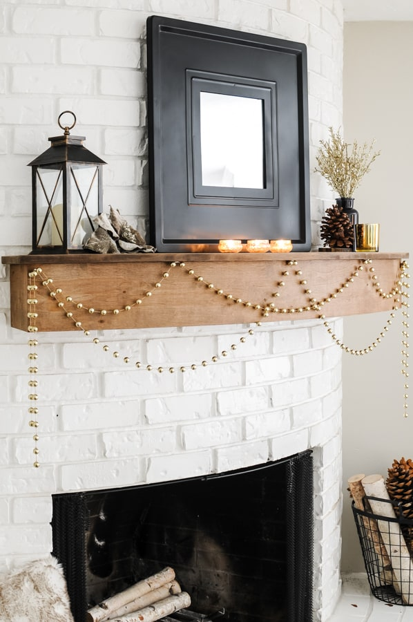 Close up of round fireplace mantel with black mirror, candles and gold garland.